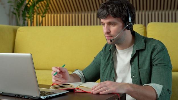 헤드폰을 착용하는 젊은 남자가 집에서 노란색 소파에 앉아 노트북의 비디오 링크에 대해 이야기하고 있습니다.