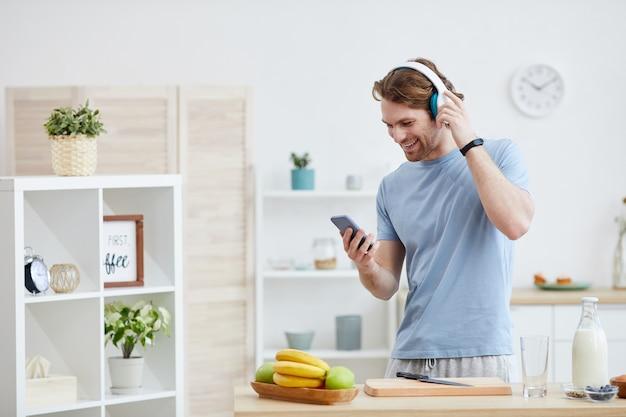 キッチンに立って携帯電話で話している間笑顔のヘッドフォンを身に着けている若い男