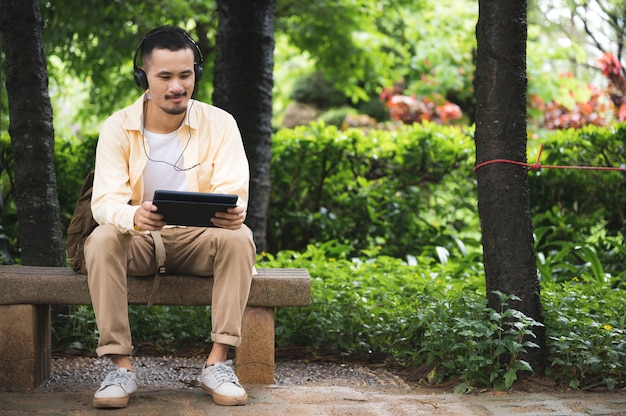 A young man wearing headphones and using a tablet in the park relaxing atmosphere after a horrible disease outbreak
