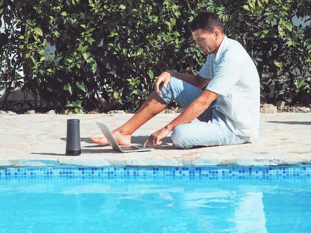 Young man wearing jeans and a shirt is working with a laptop near the swimming pool
