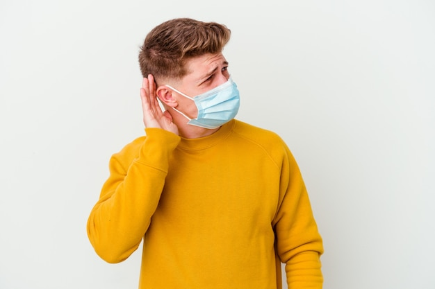 Young man wearing a mask for coronavirus isolated on white wall trying to listening a gossip.