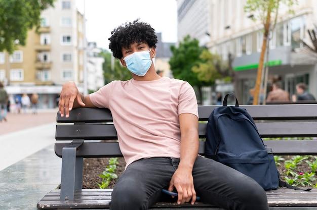 屋外でマスクを身に着けている若い男