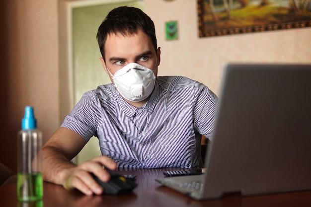 木製のテーブルの上のラップトップでコロナウイルスの発生、家庭環境を背景にリモートワークのために自宅のオフィスから職場で医療フェイスマスクを身に着けている若い男。