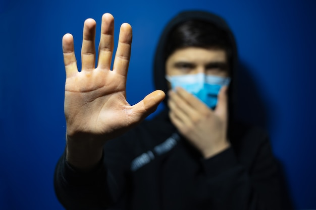 医療インフルエンザマスクとフード付きセーターを着て、青い色の壁に停止ジェスチャーを示す若い男。