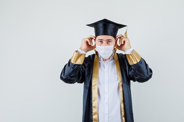 卒業式の制服を着た医療用マスクを着用し、注意深く見ている若い男。正面図。