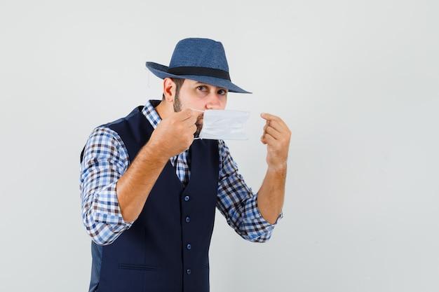 Giovane uomo che indossa la mascherina medica in camicia, gilet, cappello e guardando attento.