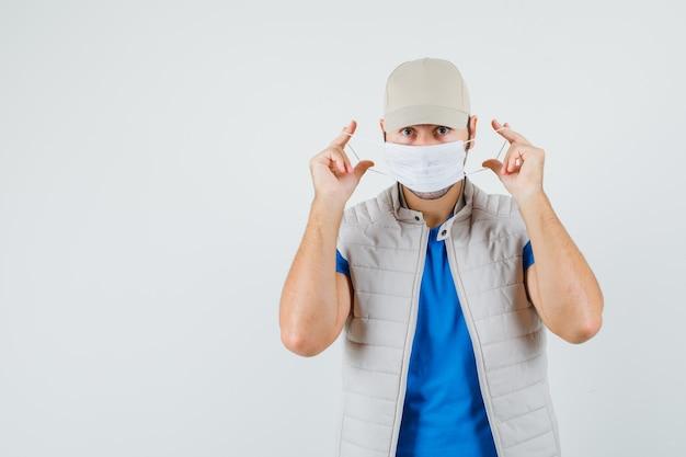 Giovane uomo che indossa la mascherina medica in t-shirt, giacca e guardando attento. vista frontale.