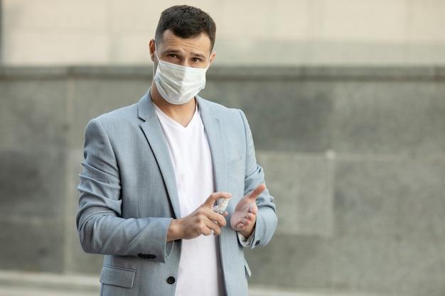 Молодой человек в медицинской маске с гелем для дезинфекции рук гуляет по городу