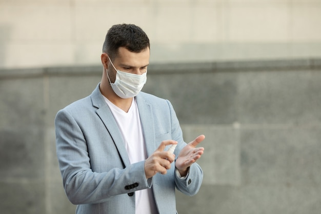 Young man wearing medical mask using hand sanitizer gel walking at the city