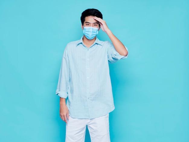 頭を抱えながら医療用マスクを着用した青年。ウイルス防止