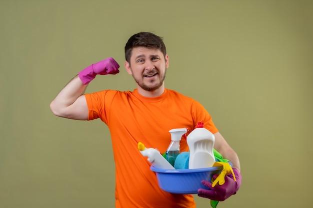 Молодой человек в оранжевой футболке и резиновых перчатках держит таз с уборкой, улыбаясь, показывая бицепсы, готовые к чистке, стоя на зеленом фоне