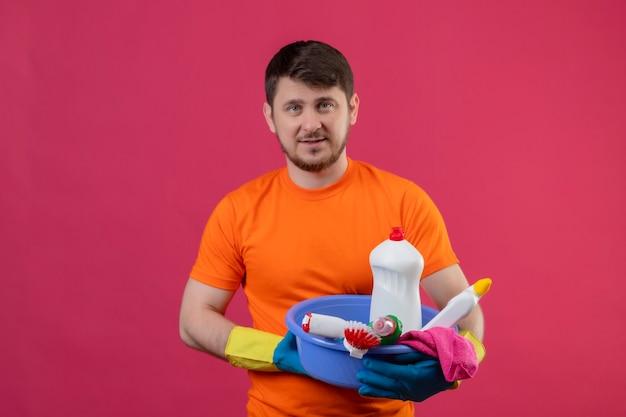 Молодой человек в оранжевой футболке и резиновых перчатках держит таз с уборкой, улыбаясь, стоя над розовой стеной