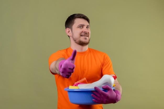 オレンジ色のtシャツとゴム製の手袋を着用して洗面器をクリーニングツールを着ている若い男