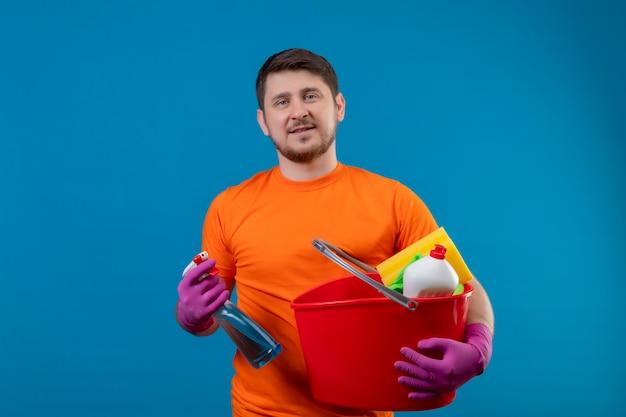 オレンジ色のtシャツとバケツを保持しているバケツをクリーニングツールとクリーニングスプレーを着ている若い男