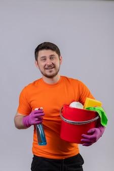 Молодой человек в оранжевой футболке и резиновых перчатках держит ведро с чистящими средствами и чистящим спреем