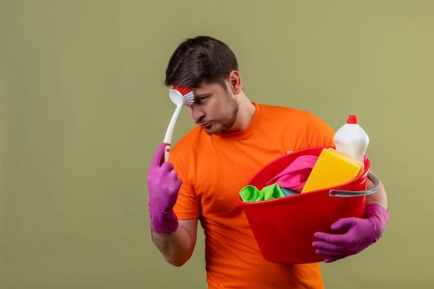 オレンジ色のtシャツとバケツクリーニングツールとスクラブブラシを保持しているゴム手袋を着用して若い男