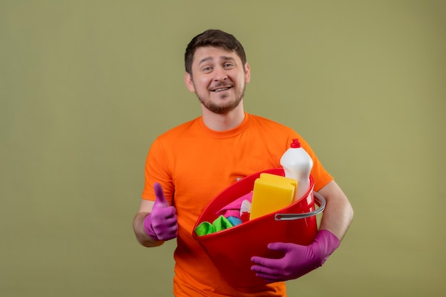 オレンジ色のtシャツとバケツを保持しているゴム手袋を身に着けている若い男の笑顔ツール陽気に肯定的で幸せな笑みを浮かべて親指を緑の壁2の上に立って