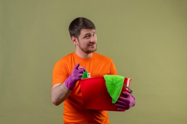 Молодой человек в оранжевой футболке и резиновых перчатках держит ведро с инструментами для уборки, улыбаясь, указывая пальцем в камеру, счастливым и позитивным положением над зеленой стеной