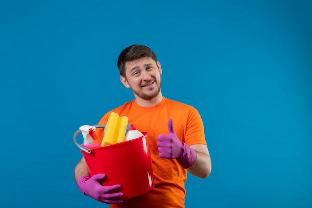クリーニングツールとバケツを保持しているオレンジ色のtシャツとゴム手袋を着用して若い男