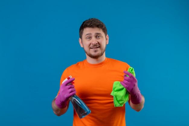 Молодой человек в оранжевой футболке и резиновых перчатках держит чистящий спрей и коврик
