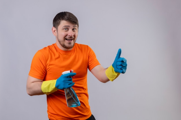 オレンジ色のtシャツとゴム手袋を着用して陽気な笑顔のクリーニングスプレーを保持している若い男