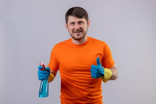 クリーニングスプレー笑顔を保持しているオレンジ色のtシャツとゴム手袋を身に着けている若い男