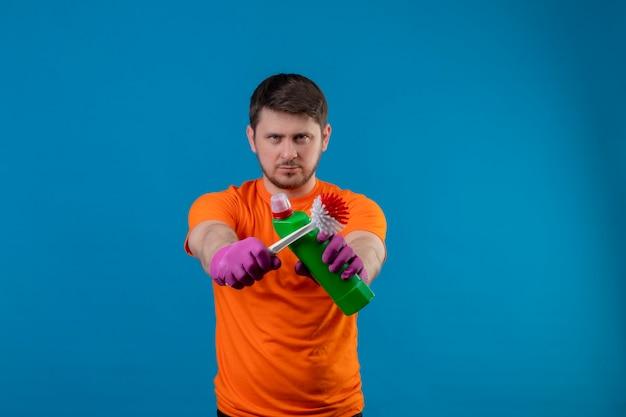 若い男がオレンジ色のtシャツとゴム手袋を着用してクリーニング用品とスクラブブラシを保持
