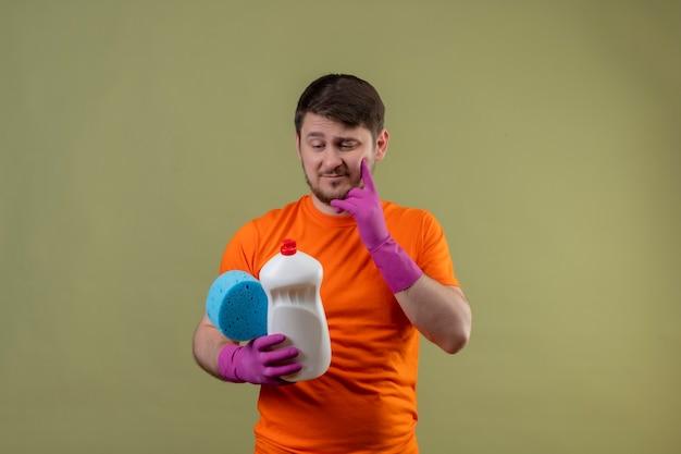 Молодой человек в оранжевой футболке и резиновых перчатках держит чистящие средства и губку, глядя на них с задумчивым выражением лица, думая, стоя над зеленой стеной