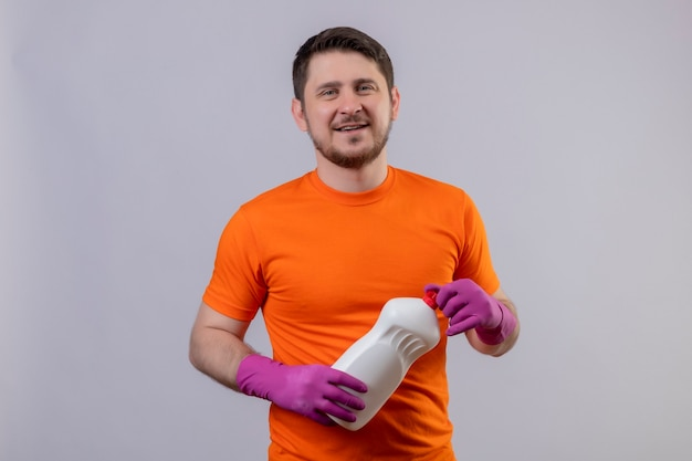 Молодой человек в оранжевой футболке и резиновых перчатках держит чистящие средства, улыбаясь позитивно и счастливо, стоя над белой стеной