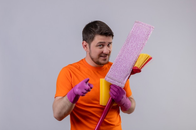 Молодой человек в оранжевой футболке и резиновых перчатках держит инструменты для уборки, улыбаясь и позитивно указывая пальцем на камеру, стоя над белой стеной