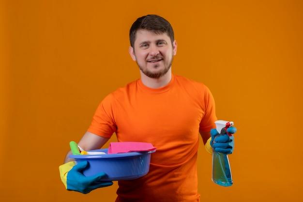オレンジ色の背景2の上に立っているをきれいにする準備ができてカメラを見て幸せで準備ができてカメラを見て笑みを浮かべてクリーニングツールと洗浄スプレーで盆地を保持しているオレンジ色のtシャツを着ている若い男