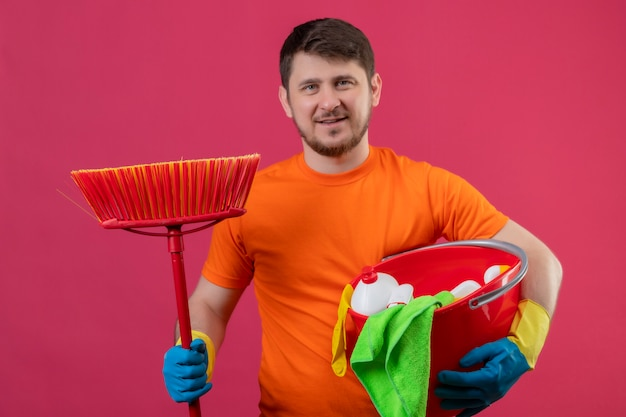 Giovane uomo che indossa la t-shirt arancione tenendo la benna con strumenti di pulizia e mop sorridente guardando la telecamera positivo e felice pronto per la pulizia in piedi su sfondo rosa