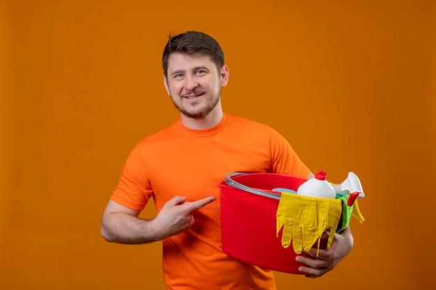 Giovane uomo che indossa la t-shirt arancione tenendo la benna con strumenti di pulizia puntando con il dito ad esso sorridente guardando la telecamera positivo e felice pronto per la pulizia in piedi su sfondo arancione
