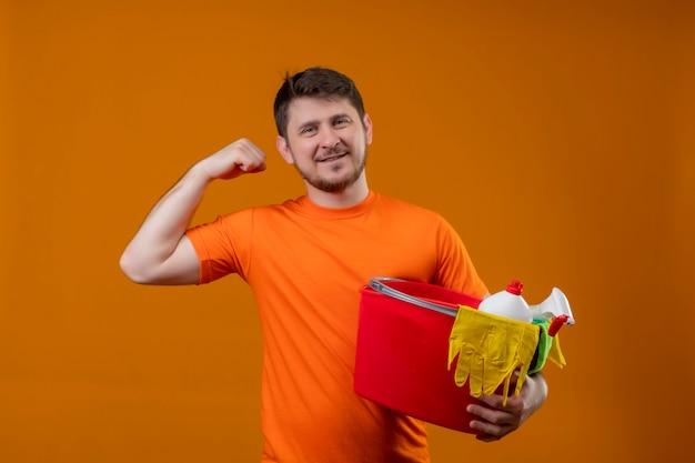 Giovane uomo che indossa la t-shirt arancione tenendo la benna con strumenti di pulizia alzando il pugno sorridente guardando la telecamera positivo e felice gioire del suo successo pronto per pulire in piedi su sfondo arancione