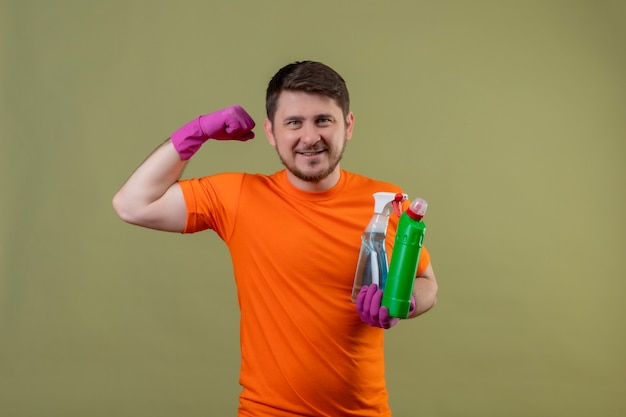 Giovane uomo che indossa la maglietta arancione e guanti di gomma per la pulizia dei materiali di consumo sorridendo allegramente positivo e felice che mostra i bicipiti pronti per la pulizia in piedi sopra la parete verde