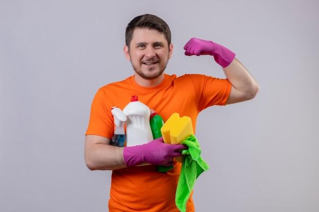 Giovane uomo che indossa maglietta arancione e guanti di gomma strumenti di pulizia sorridendo allegramente positivo e felice mostrando bicipite