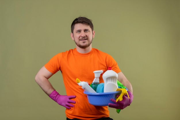 Young man wearing orange t-shirt and rubber gloves holding basin with cleaning tools smiling positive and happy standing over green wall 2