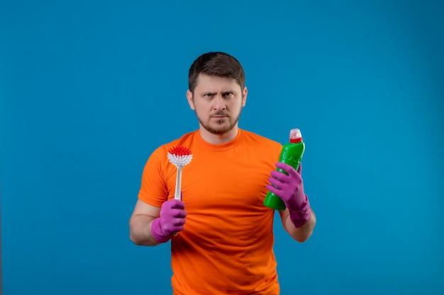 Giovane uomo che indossa la maglietta arancione e guanti di gomma che tiene la bottiglia con prodotti per la pulizia e spazzola