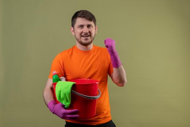 Giovane uomo che indossa maglietta arancione e guanti di gomma che tiene secchio con strumenti di pulizia che stringono il pugno felice ed è uscito sorridendo allegramente rallegrandosi del suo successo in piedi sopra il muro verde