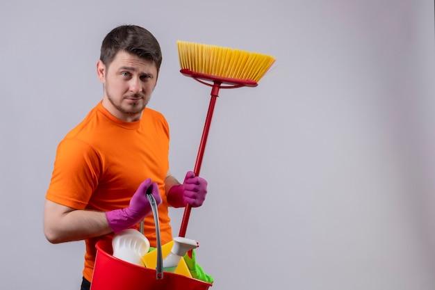 Giovane uomo che indossa una maglietta arancione e guanti di gomma tenendo la benna con strumenti di pulizia e mop cercando fiducioso pronto a clen concetto in piedi sopra il muro bianco