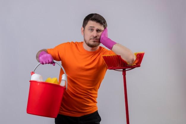 Giovane uomo che indossa maglietta arancione e guanti di gomma che tiene secchio con strumenti di pulizia e scopa che sembra stanco e annoiato in piedi sopra il muro bianco