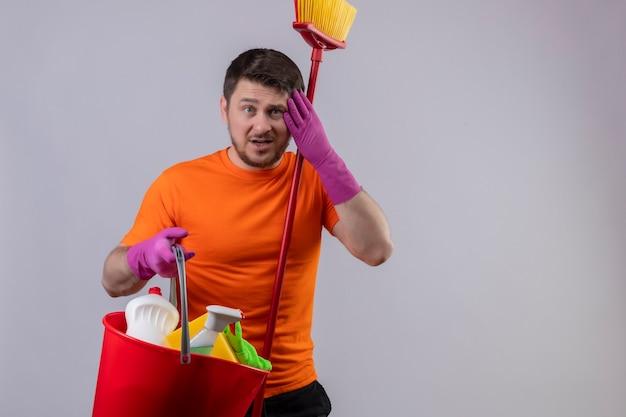 Giovane uomo che indossa maglietta arancione e guanti di gomma che tiene secchio con strumenti di pulizia e mop toccando la testa per errore cercando confuso in piedi sopra il muro bianco
