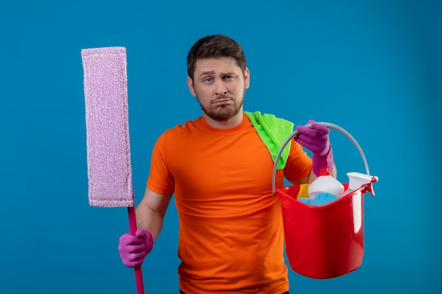 Young man wearing orange t-shirt and rubber gloves holding bucket with cleaning tools and mop