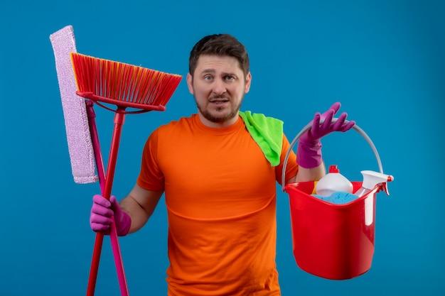 Giovane che indossa la maglietta arancione e guanti di gomma che tengono secchio con strumenti di pulizia e mop