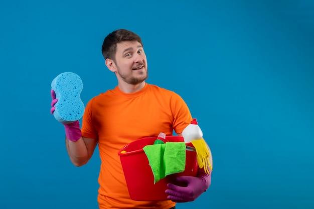 Giovane che indossa la maglietta arancione e guanti di gomma che tengono secchio con strumenti di pulizia e spugna
