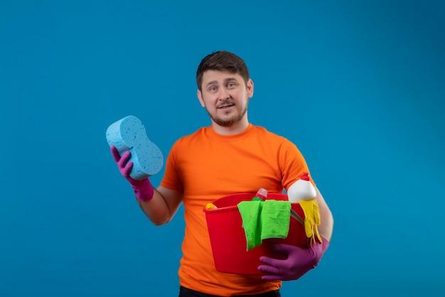 Giovane uomo che indossa maglietta arancione e guanti di gomma che tengono secchio con strumenti di pulizia