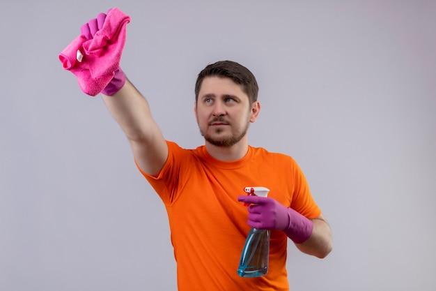 Giovane uomo che indossa la maglietta arancione e guanti di gomma che tengono spray per la pulizia e tappeto a guardarlo