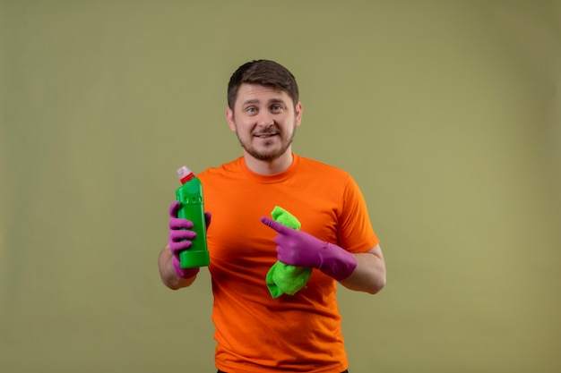 Young man wearing orange t-shirt and rubber gloves holding cleaning spray and rug pointing with finger to bottle with spray smiling cheerfully positive and happy looking at camera on green background