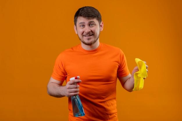 Giovane uomo che indossa maglietta arancione e guanti di gomma che tengono spray per la pulizia e tappeto sorridendo allegramente