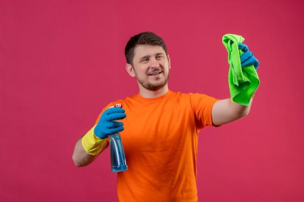 Giovane uomo che indossa la maglietta arancione e guanti di gomma tenendo spray per la pulizia e rug sorridente guardando rug pronto per la pulizia in piedi sopra il muro rosa